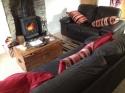Spacious living room with woodburner and leather sofas