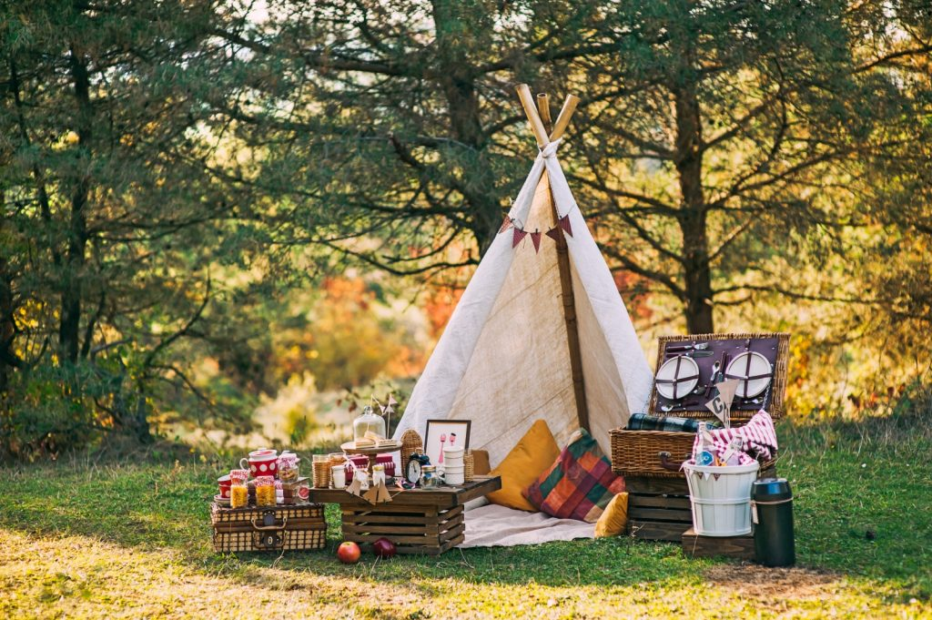 Little white wigwam amongst the trees with picnic hampers in front