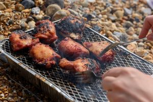 disposable BBQ on pebble beach cooking chicken thighs