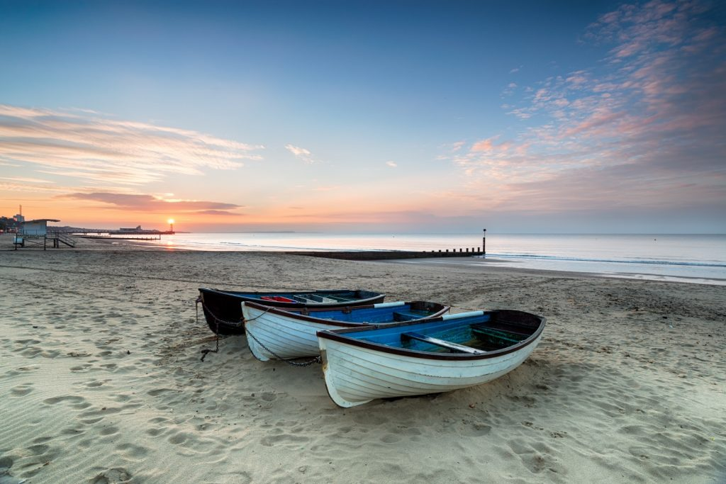 Three small boats on the sandy beach with sun setting behind