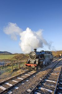 Steam trail on tracks going through countryside steaming