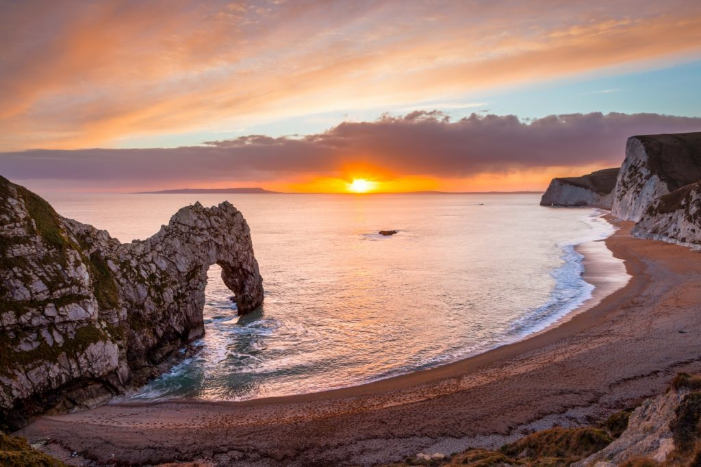 Sun setting over the sea with Durdle Door stone arch in the sea by the sandy beach