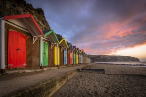 Brick beach huts with colourful doors  (red, yellow, blue) alongside the beach with a moody red night sky