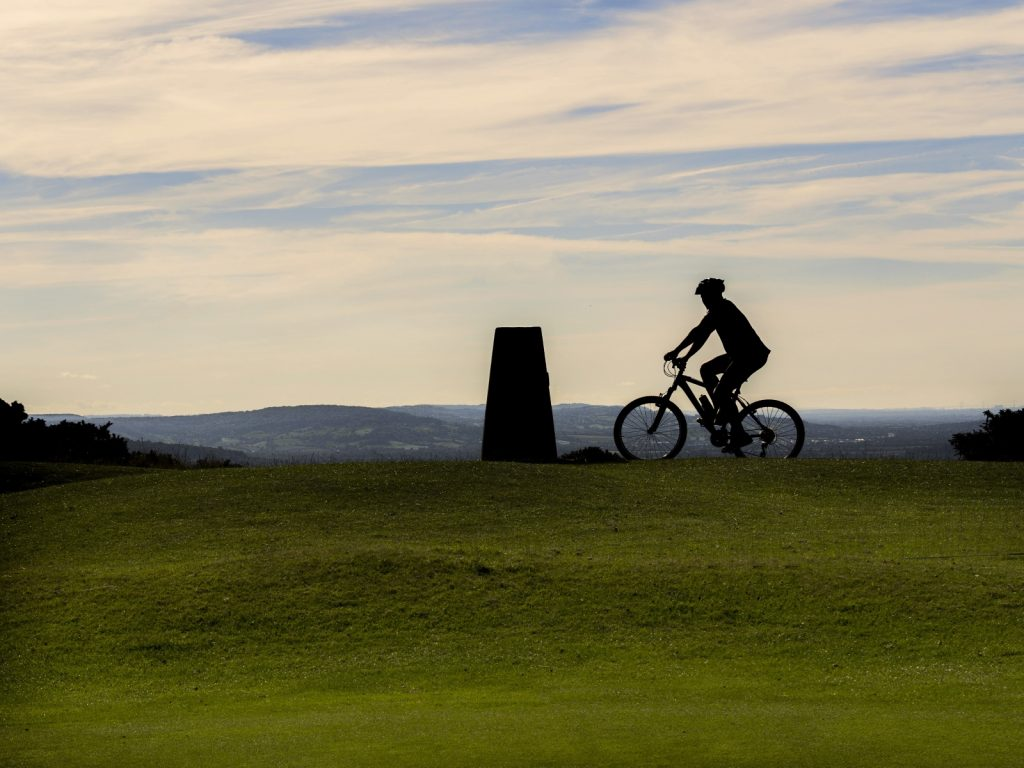Silhouette of mountain biker at top of grass hill by monument