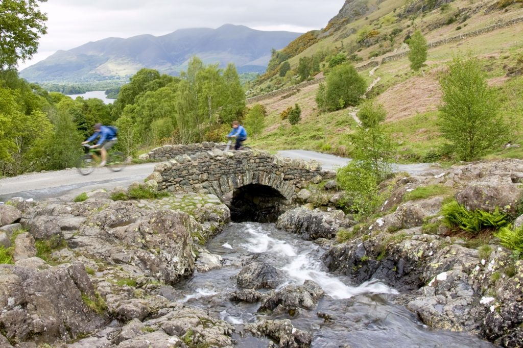 Two cyclists going over bridge that straddles stream with mountains in back ground