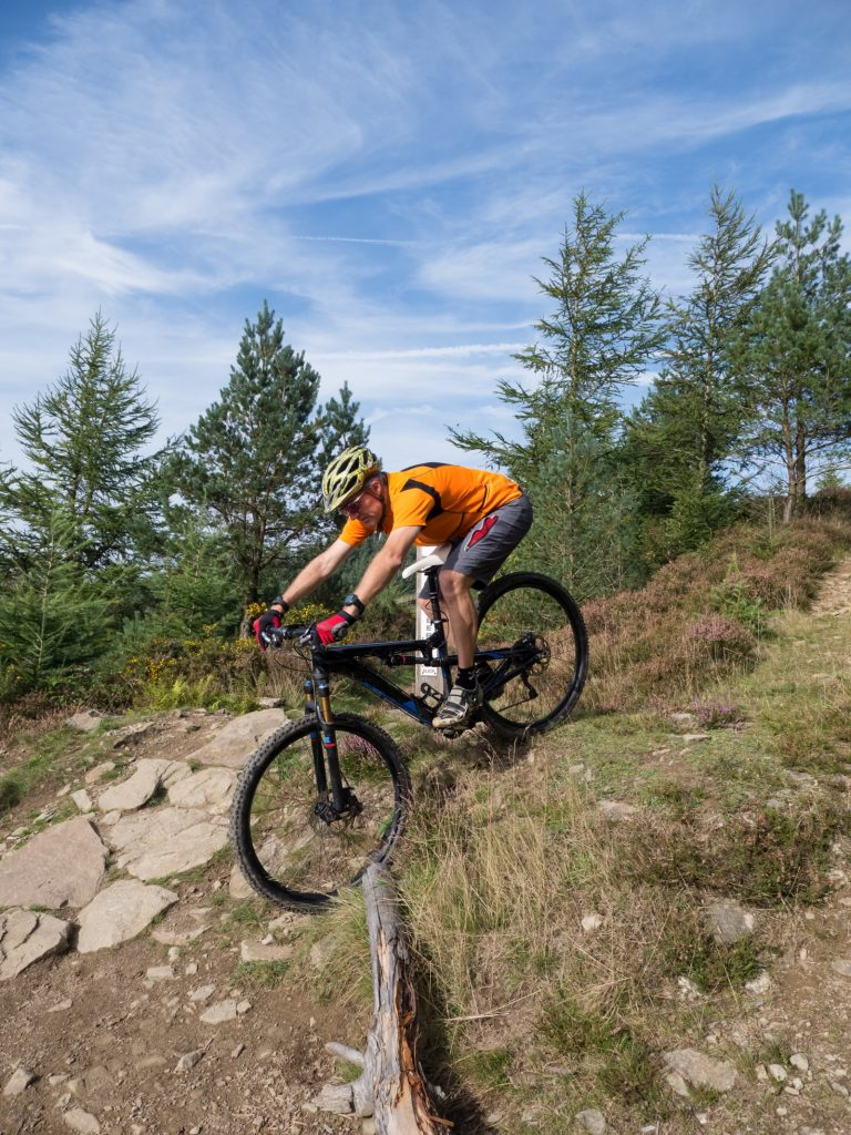 Man in orange shirt on mountain bike going down stoney slope with trees