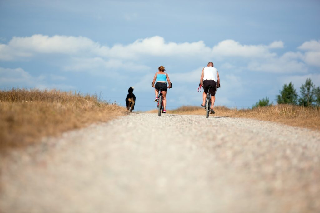 Man and women cycling along a track with dog to the side