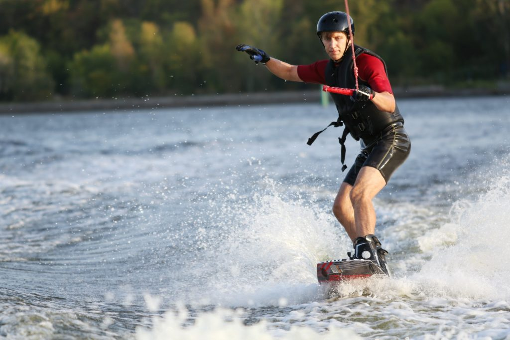 Man standing on a wake board on a lake