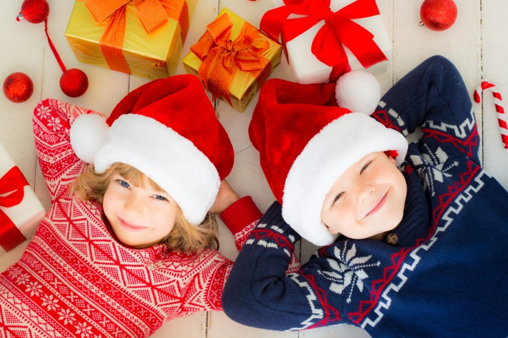 Small boy and girl laying amongst presents with Christmas Santa hats on