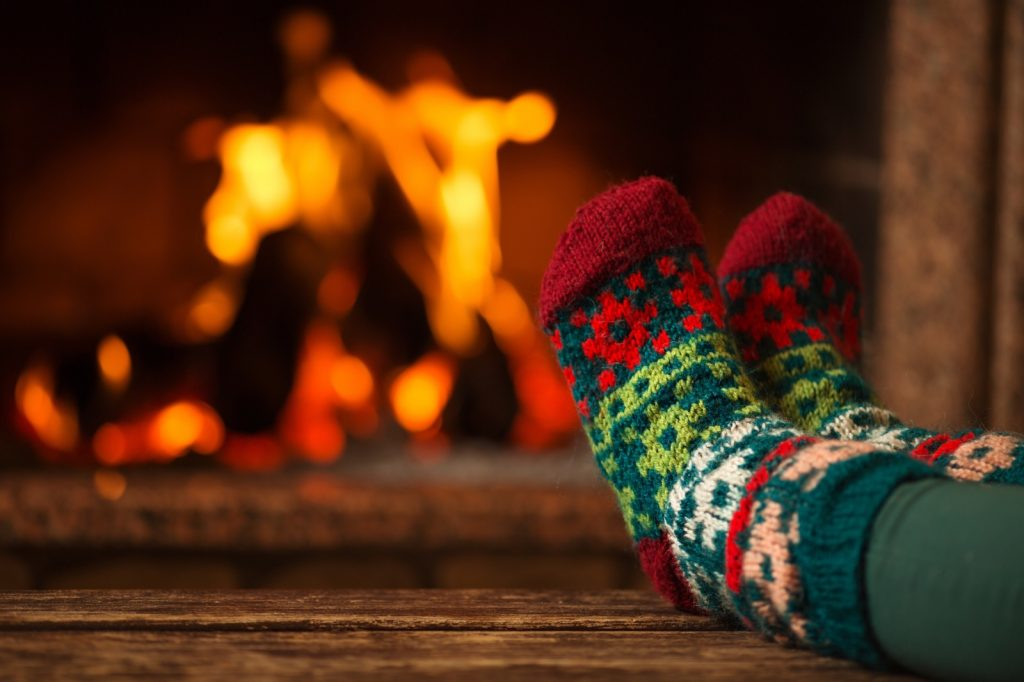 Feet in Christmas socks up on a table in front of a fire