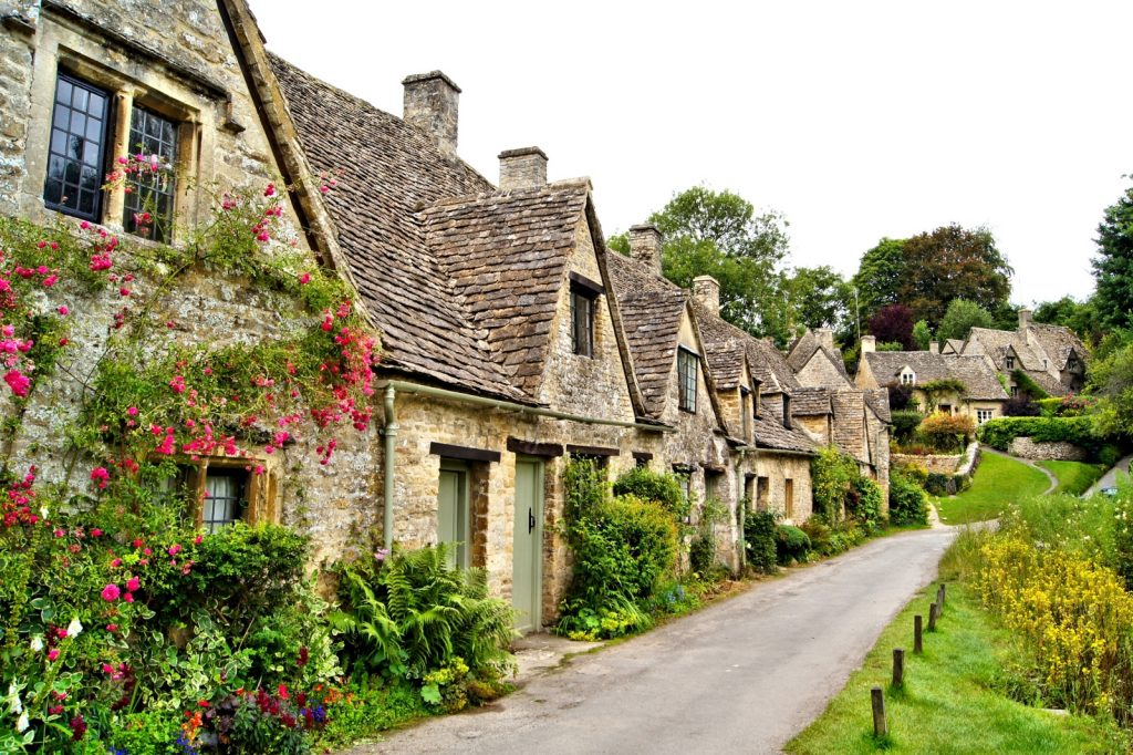 Row of honey coloured cottages, some clad with flowers