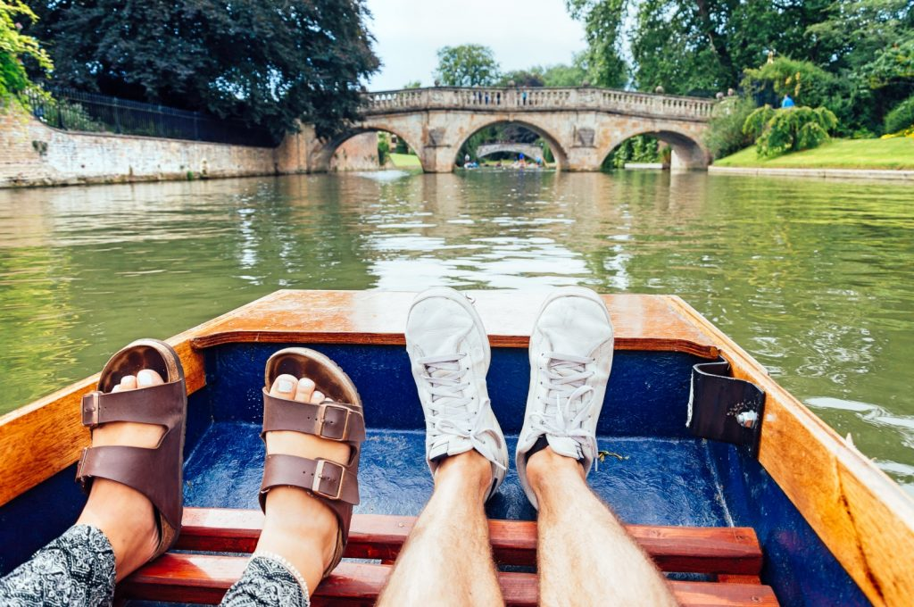 A mans and ladies feet looking down a punting boat, and river to a historic bridge in the distance