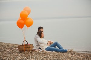 Couple cuddling on pebble beach looking out to see with picnic basket with orange balloons tied to handle