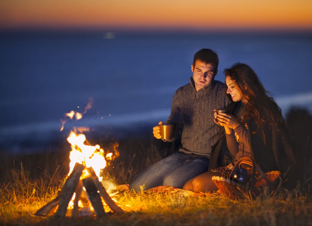 Couple sitting by a fire beside the sea of a night with mugs in hand