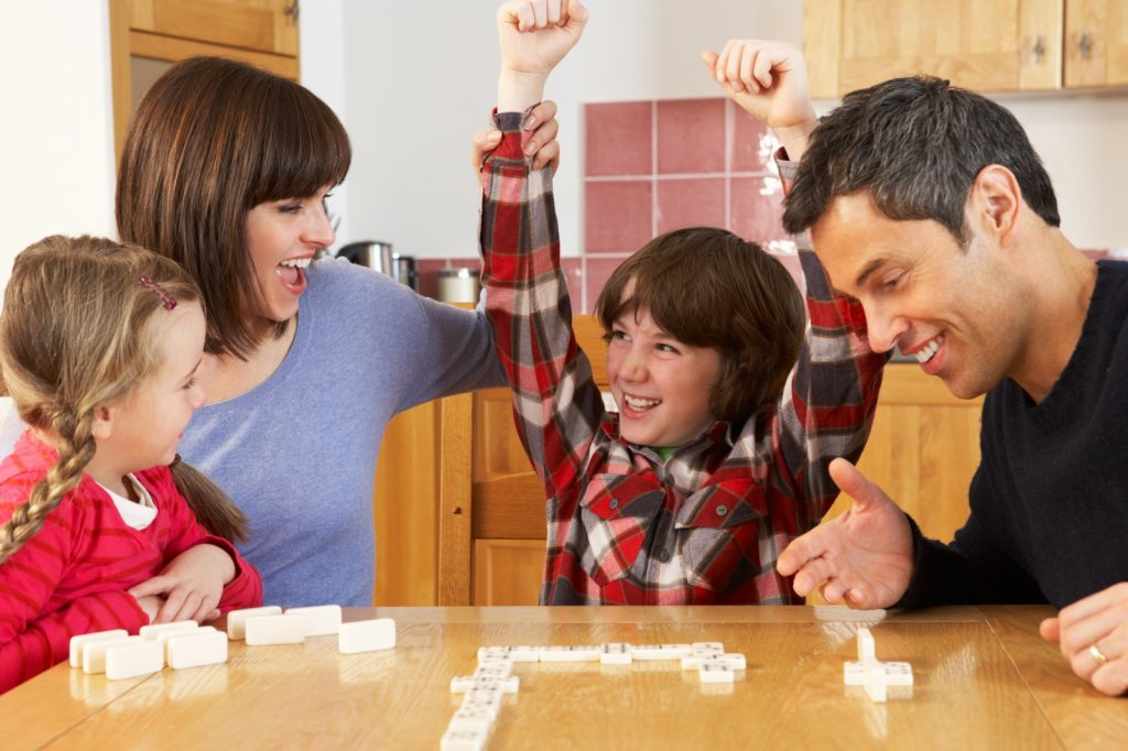 Family sitting around table playing scrabble with boy throwing arms in air celebrating victory