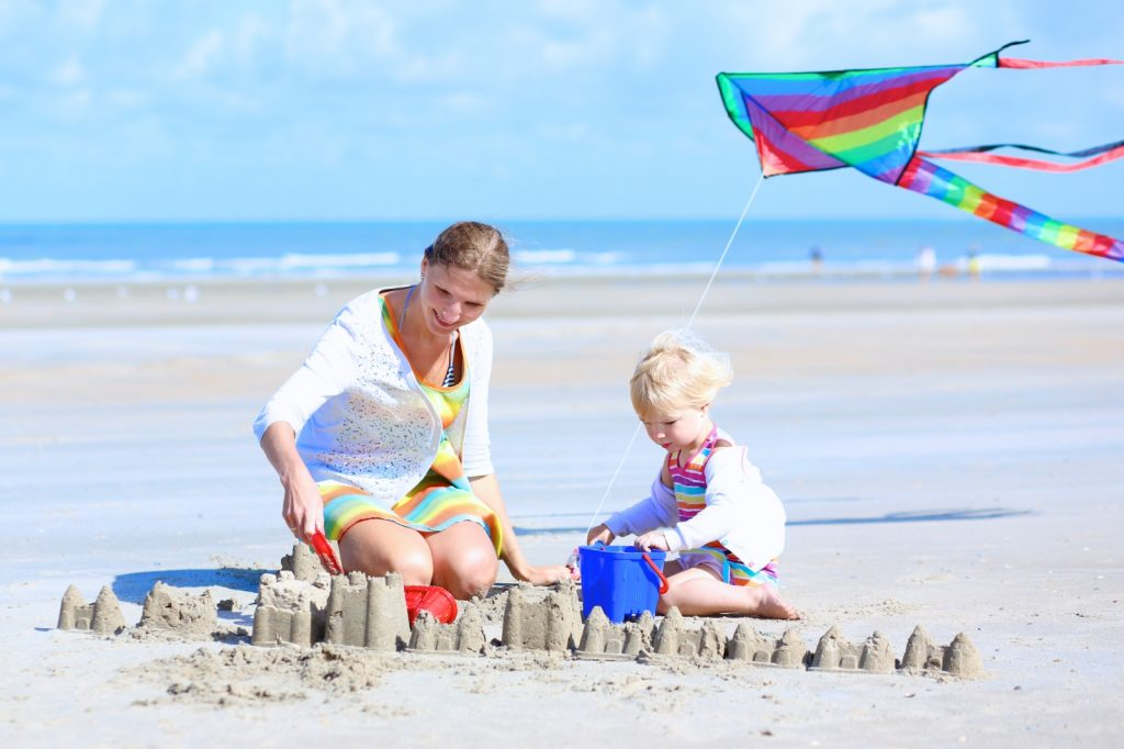 Mother and small child sitting on a sandy beach building sand castles with colourful kite flying above
