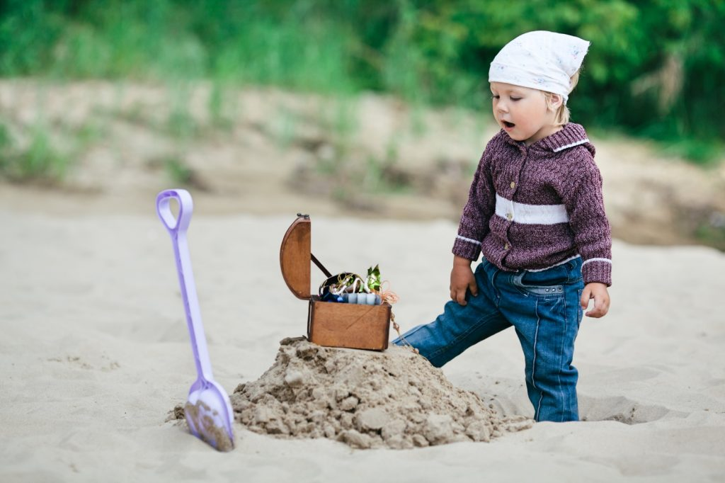 Child looking surprised at small treasure chest dug up on beach
