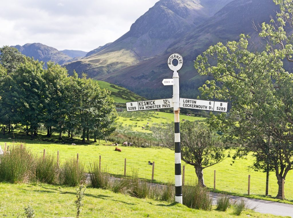Sign post to Keswick with field and mountain behind