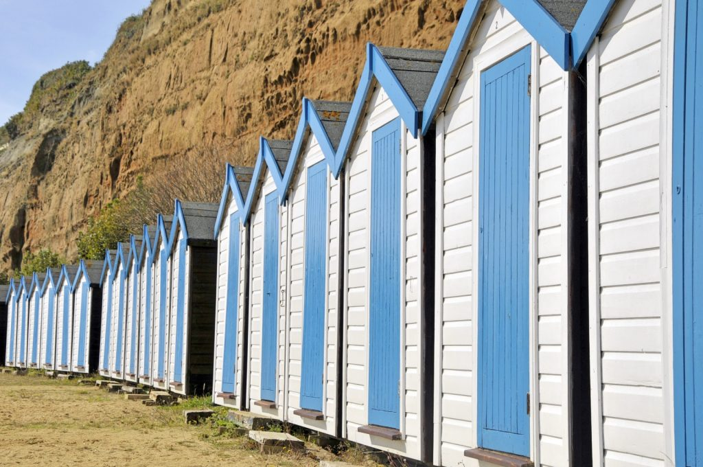 Row of blue and white beach huts against the cliffs