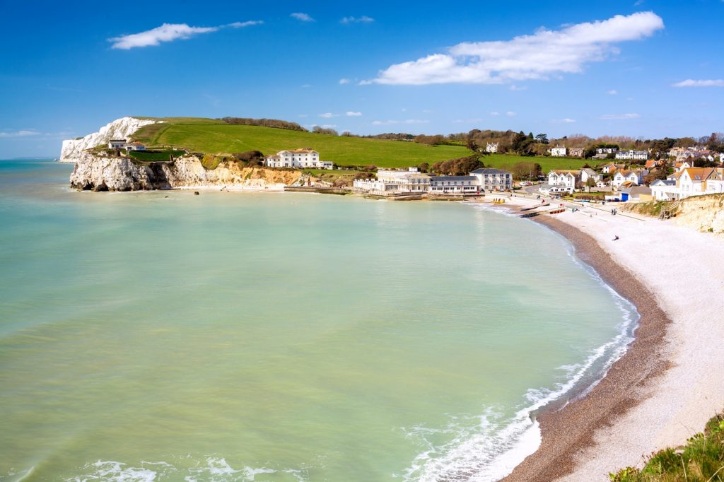 Turquoise waters against the white beach of Freshwater Bay, fringed by white cliffs and rolling countryside