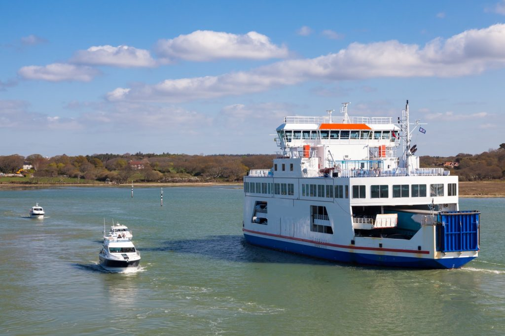 White & blue ferry with small boat alongside crossing the water of the Solent on sunny day with clouds in sky