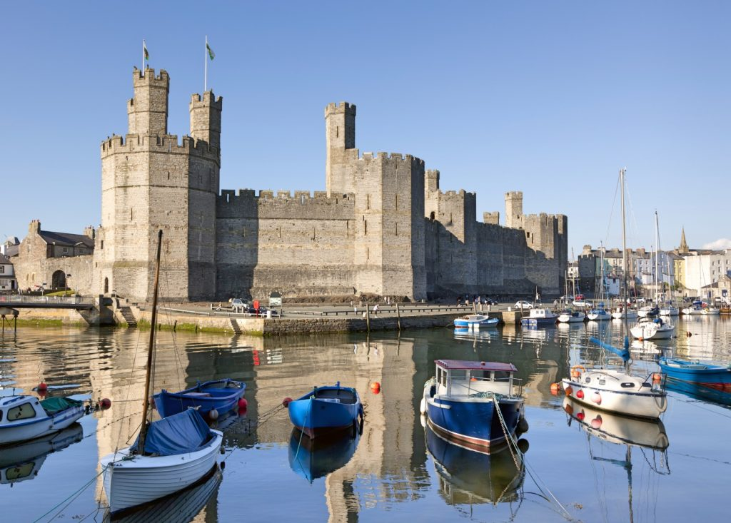 Caernarfon Castle on a sunny day with the water in front of it & boats