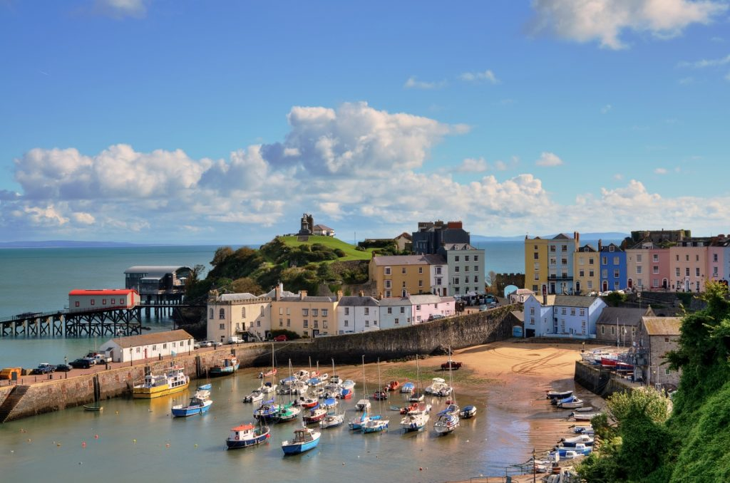 Boats on the harbour water of Tenby with small beach and colourful pastel coloured houses