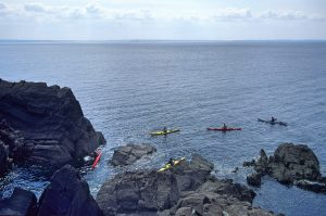 People kayaking around the rocks