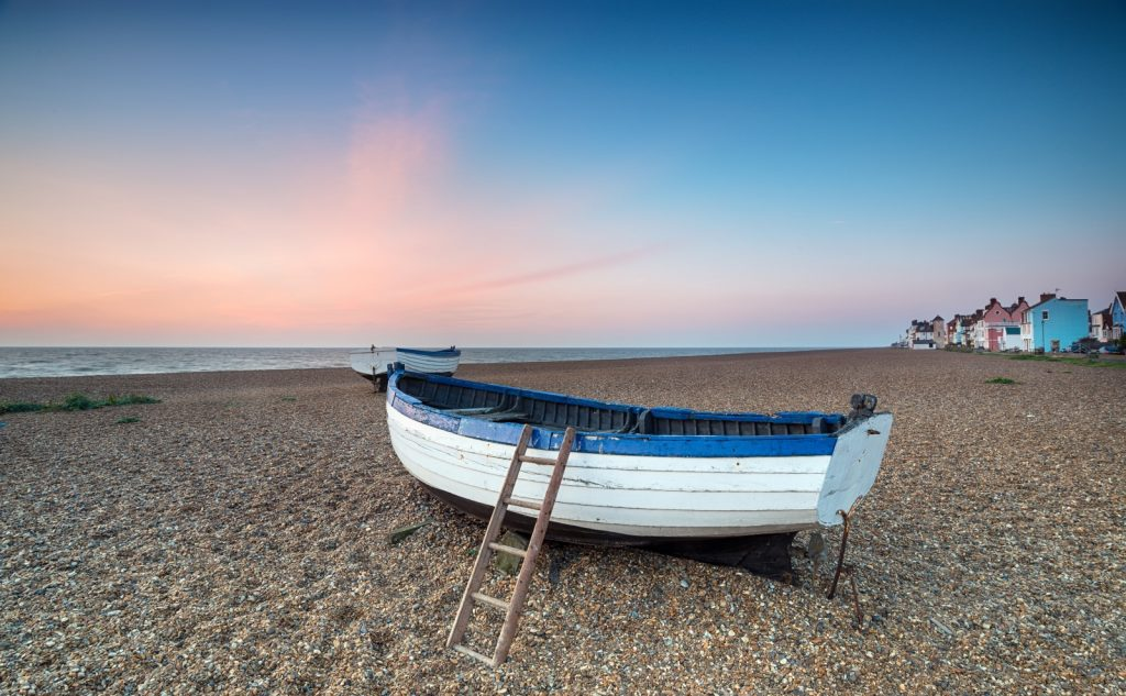 Blue and white fishing boat on the shingle beach with pink tinged sky