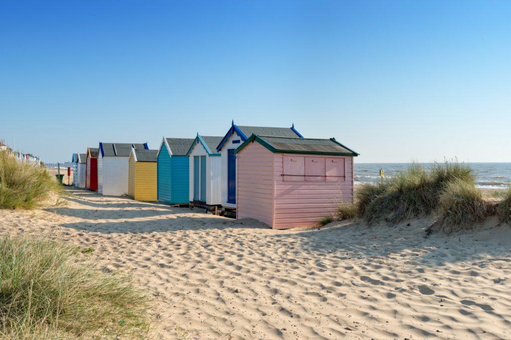 Colourful beach huts on sandy beach