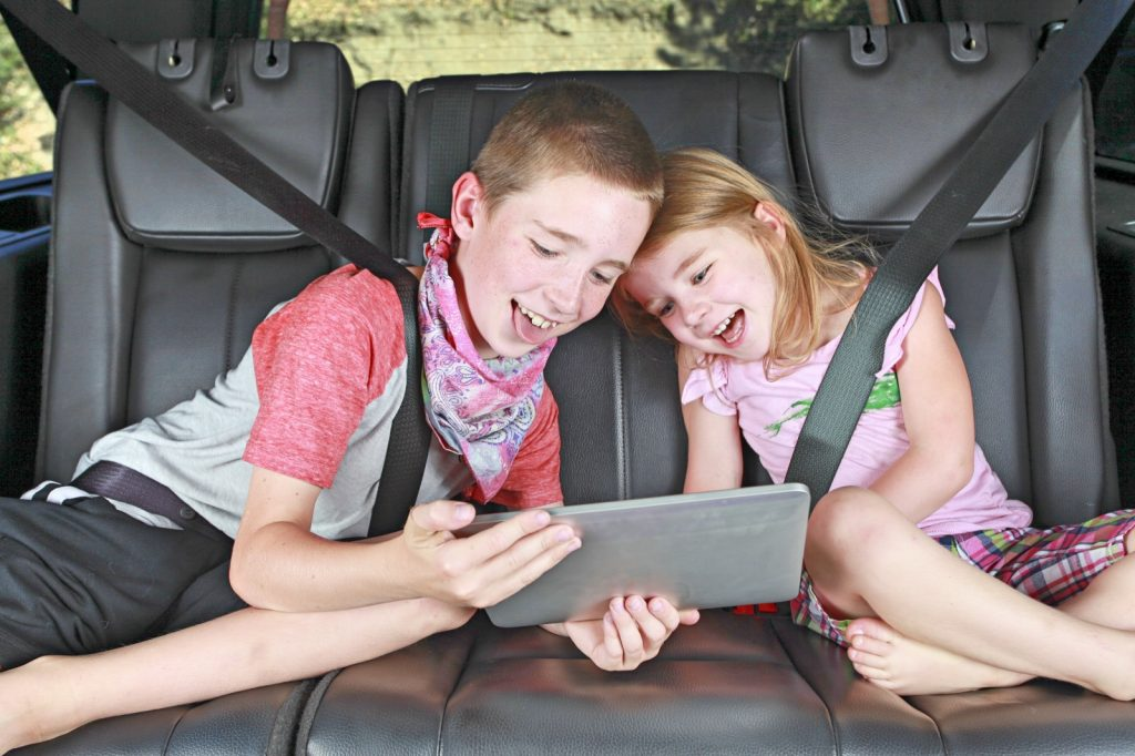 Boy and younger girl sitting on the back seat of a car looking at a computer screen laughing