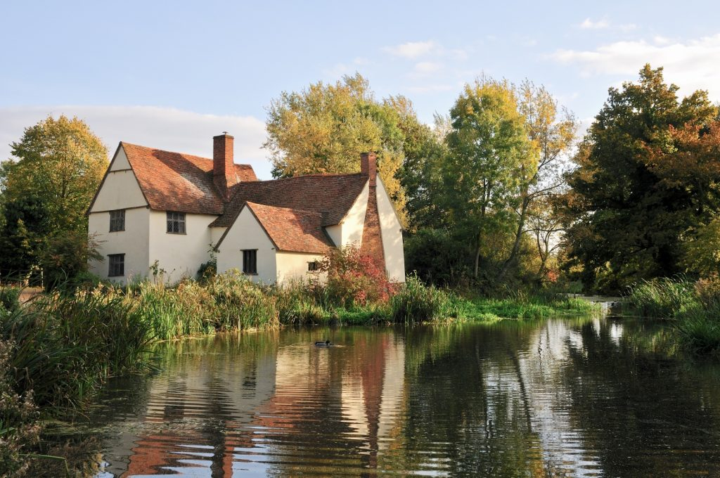River with the sunshine creating reflections of the old cream painted house behind with red tiled roof