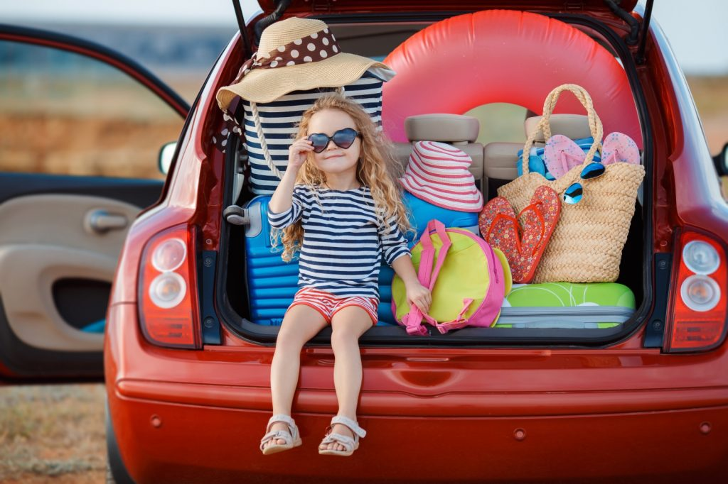 Little girl with heart shaped glasses on sitting in the boot of a car stacked with cases, sun hats and beach gear
