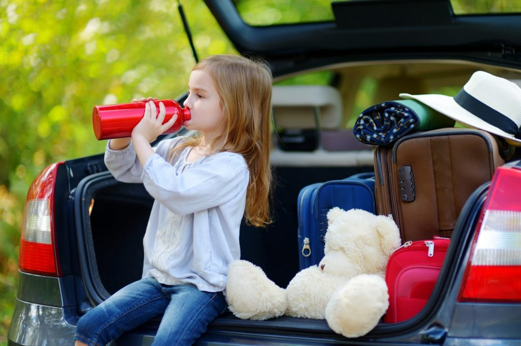 Little girl sitting in the boot of a car drinking out of a bottle with teddy and suitcases