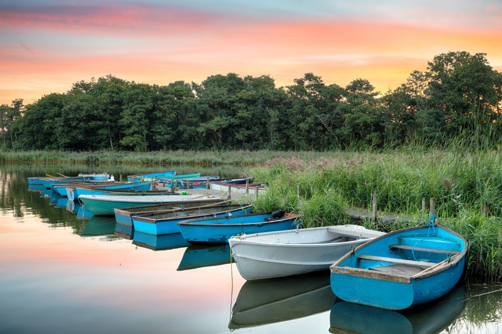 Blue and white rowing boats moored up on the river with trees and sun setting behind