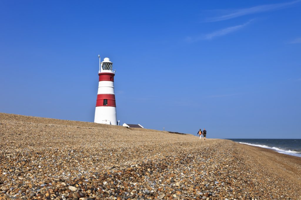 Couple walking along shingle beach with red and white lighthouse above