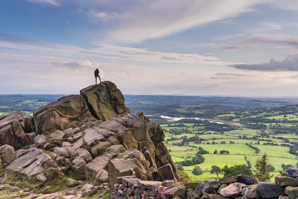 Man on top of rocks overlooking rolling green countryside