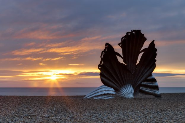 A scallop shell sculpture on the shingle beach with sun setting behind