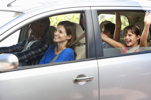 Parents sitting in a car smiling with kids in the back waving