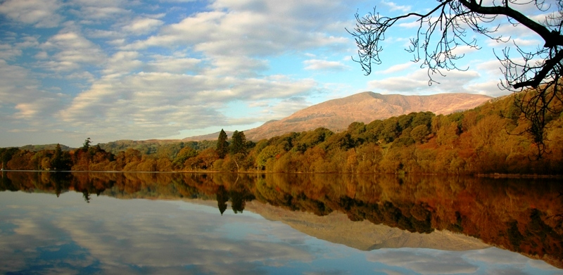 Views over Coniston lake with autumnal trees and mountains at the edge & blue cloudy sky that is reflected in the water