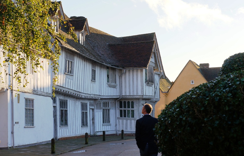 Man looking up at the white and beamed Guildhall in Lavenham market square