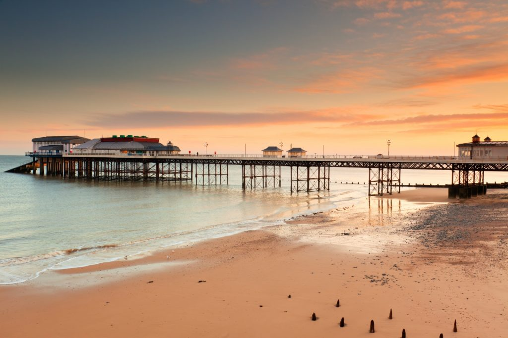 A view of cromer pier from the beach as the sun sets