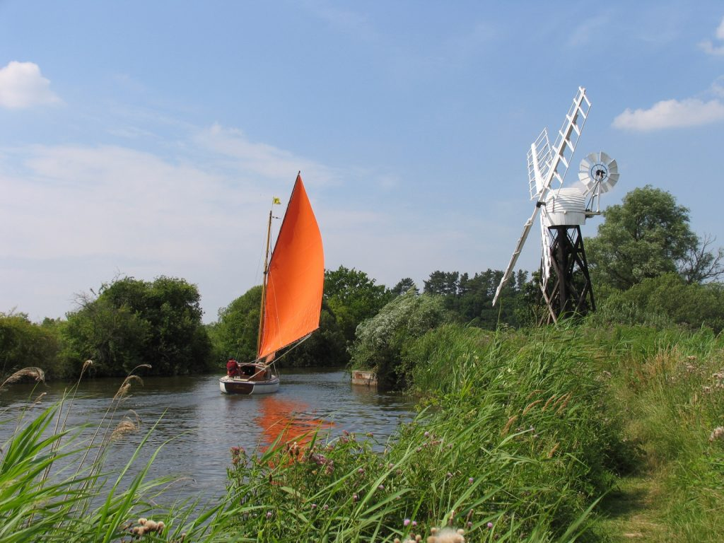 Sailing boat with orange sail on river by black and white windmill