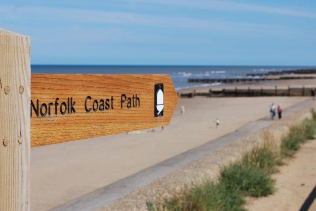 Norfolk coastal Path sign with beach behind