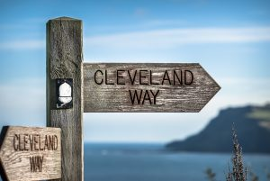 Cleveland Way wooden footpath sign with the sea in background