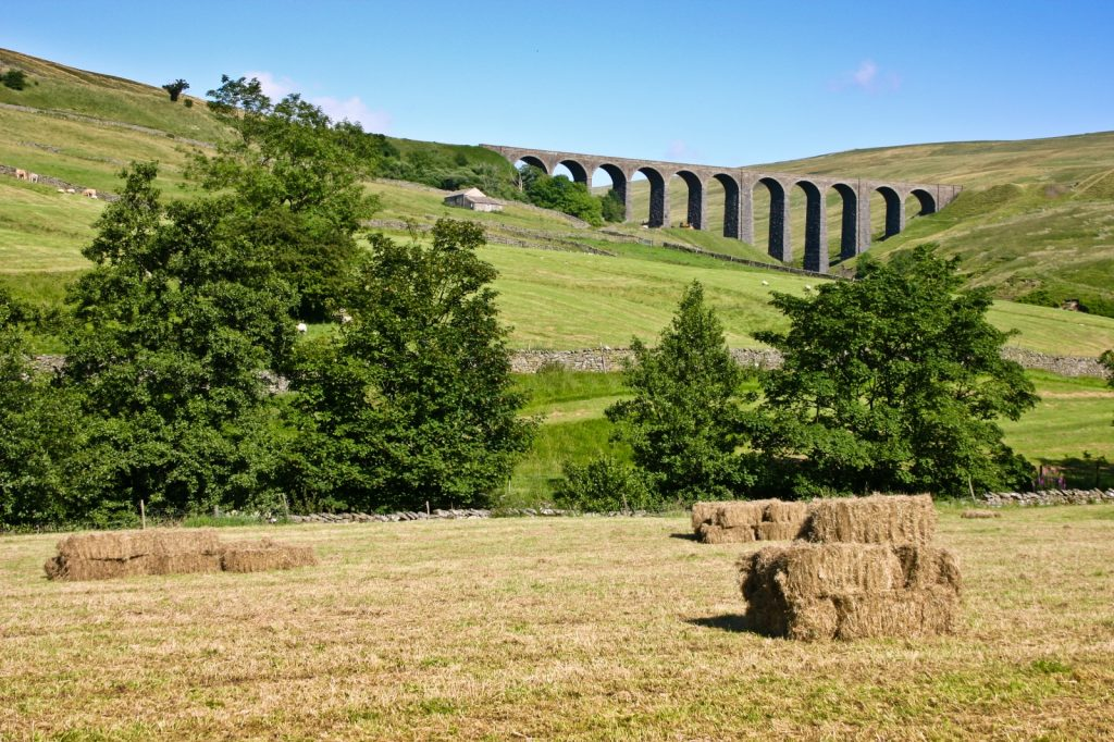Field with hay bales stacked and the Dent Viaduct up above the trees - clear blue sky