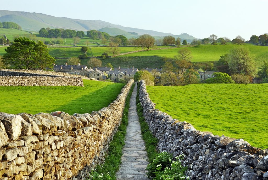 Dry stone walls each side of a long stone path take the eye to a village with stone houses in the distance with green rolling fields all around
