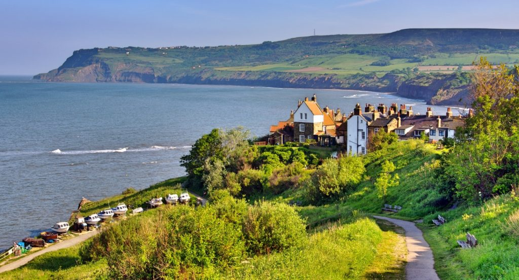 Picture of the green rolling hills around the coastline with sea to the left and houses in the forefront