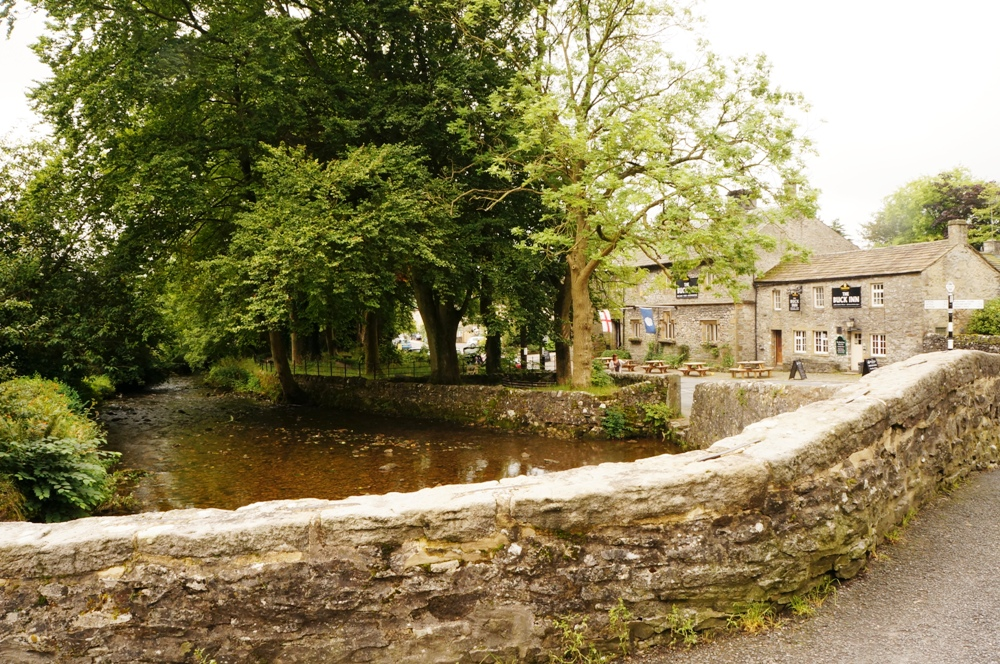 village setting with dry stone wall winding around to the village pub with stream to the left