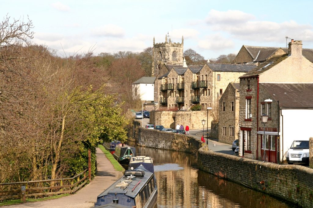 View along the canal with boats to the left and stone Dales houses to the right with church steeple in distance